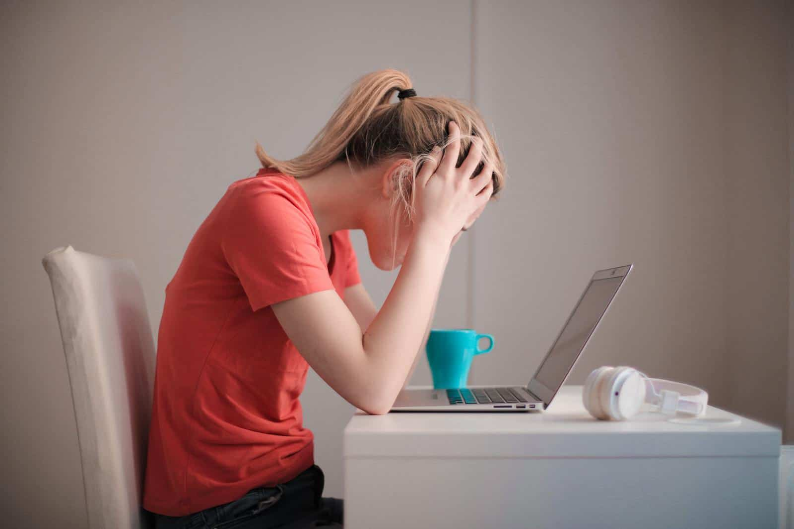 Woman holding head above laptop