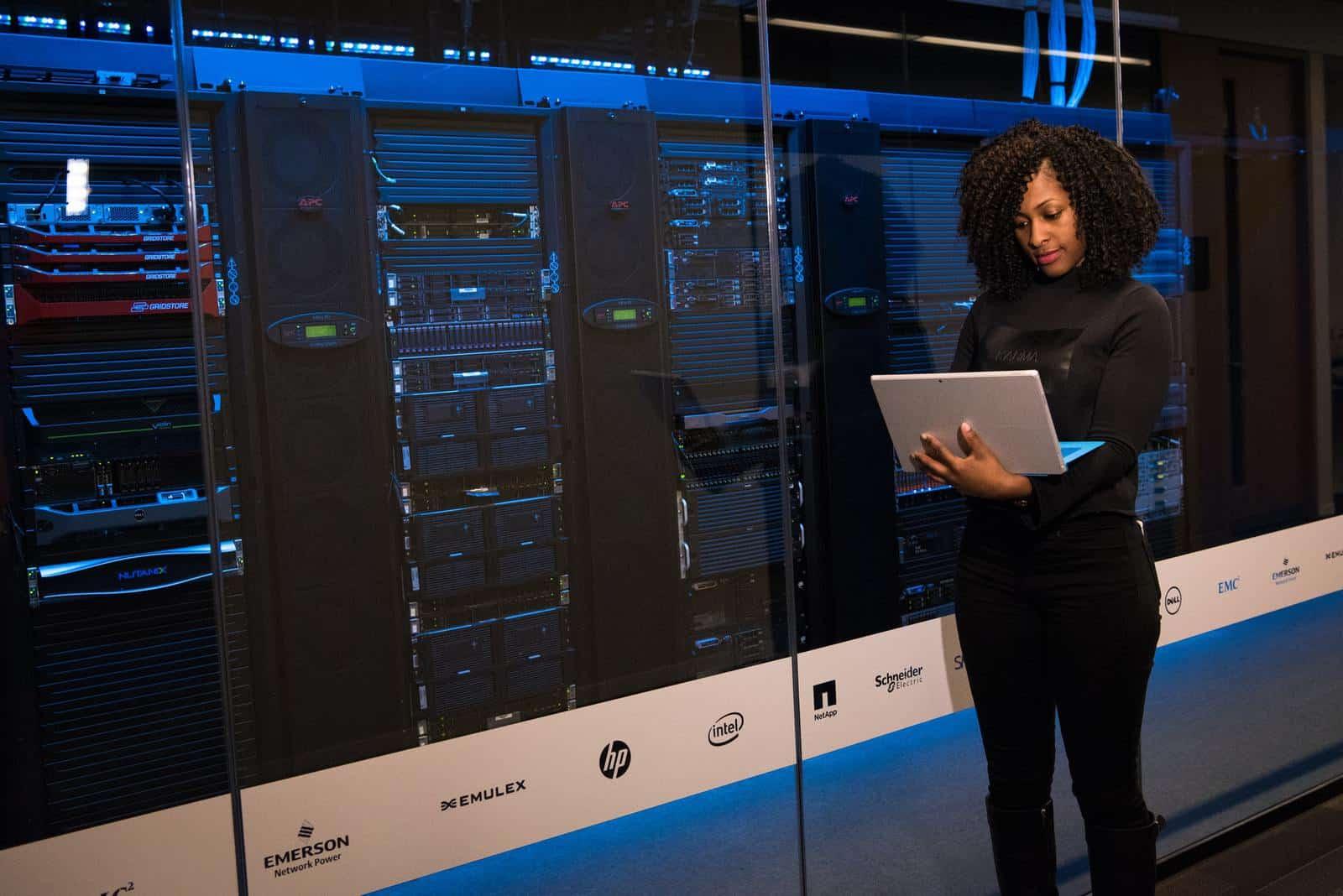 Woman using laptop next to server